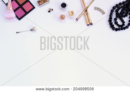 Styled fashion and beauty products frame white copy space.