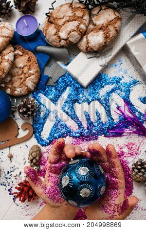 Christmas festive background reversed top view. Little kid holds ornament blue ball in purple glittering hands on xmas inscription and handmade decoration backdrop. Holiday and celebration concept
