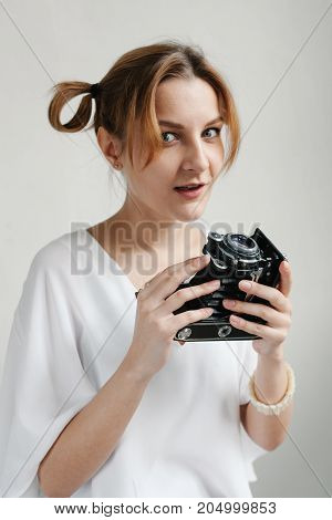 Close Up Portrait Of A Smiling Pretty Girl Taking Photo On A Retro Camera Isolated Over White Backgr