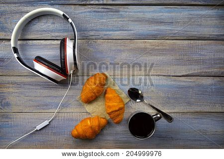 Delicious breakfast with fresh croissant and coffee. Headphones croissant and black coffee on wood table. Modern style of life. Top view.