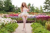 Sexy blonde woman wearing beautiful lingerie with stockings and corset, walking in blooming garden. Hot female in underware posing in sensual way outdoors. Female fashion, model fitted like a doll, barbie poster