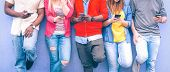 Teenagers texting mobile phone messages leaning on urban wall - Group of multiracial friends using cellular standing outdoors - Concept of students addiction to social network and telephone technology poster