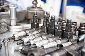 The old diesel injectors lie on the table in the fuel shop. The concept of repair of fuel diesel equipment poster