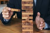 Alternative risk concept plan and strategy in business Risk To Make Buiness Growth Concept With Wooden Blocks Images of hand of businesspeople placing and pulling wood block on the tower. poster