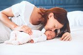 Mother kissing her newborn baby. Young beautiful mom lying at bed with a cute little sleeping child. New born baby's first days of life in family at home. Loving mother looks at asleep infant. poster