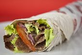 Traditional turkish doner kebab in lavash bread served on white plate poster