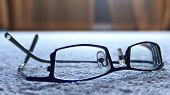a pair of modern glasses resting upside down on a soft background poster