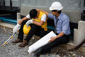 Sad Asian unemployed young foreman cry while Senior engineer manager comfort and cheer up at construction site. bad economy situation forces to layoff employees. poster