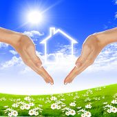 human hands holding model of a house against nature background poster