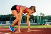 Young woman athlete at starting position ready to start a race. Female sprinter ready for sports exercise on racetrack. poster