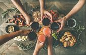 Flat-lay of friends eating and drinking together. Top view of people having party, gathering, dinner together sitting at wooden table set with wine snacks and fingerfoods. Hands with glasses clinking poster