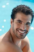 Handsome happy young hispanic man smiling and relaxing near hotel pool. Vertical shape head and shoulders poster