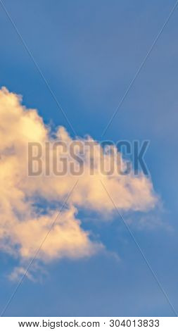 Vertical Cottony White Clouds Isolated Against A Vivid Blue Sky Background