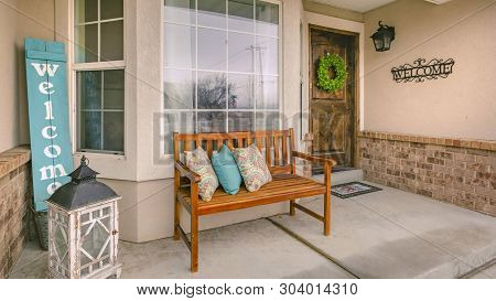 Panorama Frame Wooden Porch Bench With Pillows Against The Shiny Front Window