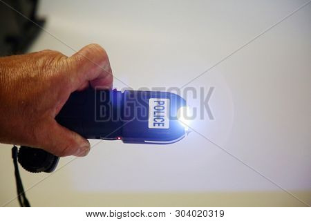 Stun Gun. Police Stun Gun. A mans hand activates a Stun Gun demonstrating the Electric Arc generated. Self Defense weapon.