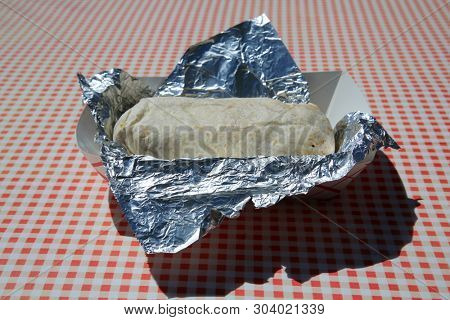 Burrito. Foil Wrapped Burrito filled with vegetables and meat. Breakfast, Lunch and Dinner foo d to go concepts.