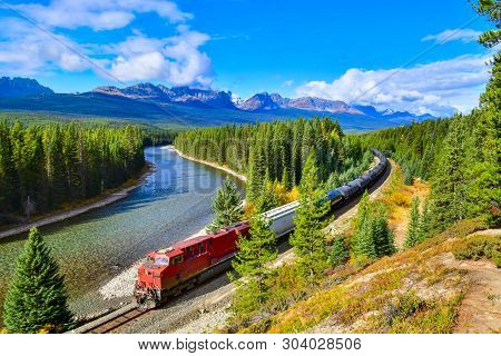 Long Freight Train Moving Along Bow River In Canadian Rockies ,banff National Park,canadian Rockies,