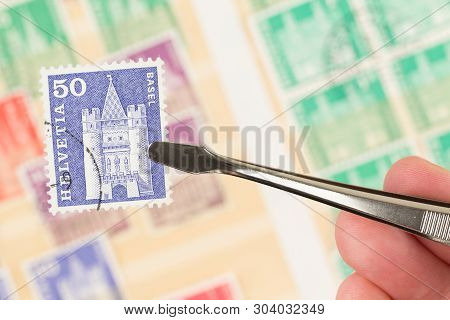 Seattle, Washington - May 29, 2019:  Hand Holding Tongs And Postage Stamp Are In Focus,  With Blurre