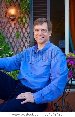 Handsome Smiling Caucasian Man In Early Fifties In Blue Shirt Sitting And Relaxing On Italian Verand