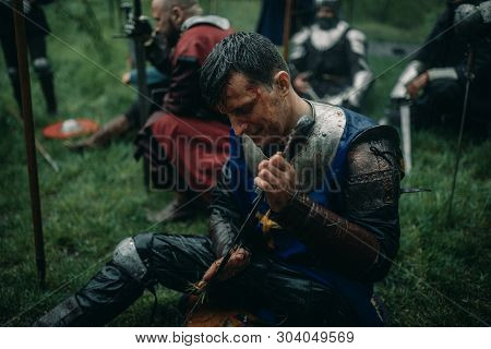 A Young Man Sits In The Image Of A Medieval Knight In Armor And Cleans His Sword During The Halt In