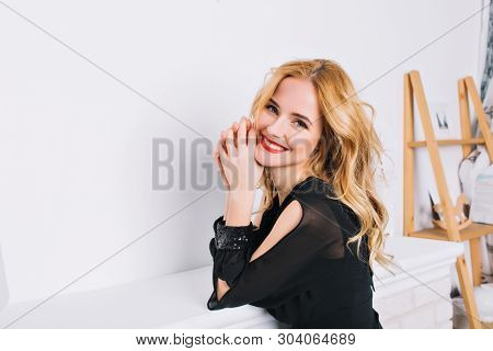 Closeup Portrait Of Girl With Blonde Wavy Hair In Modern Luxary Room, Studio. Young Woman Smiling To