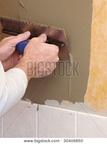 Hands on trowel spreading mortar for ceramic tile installation