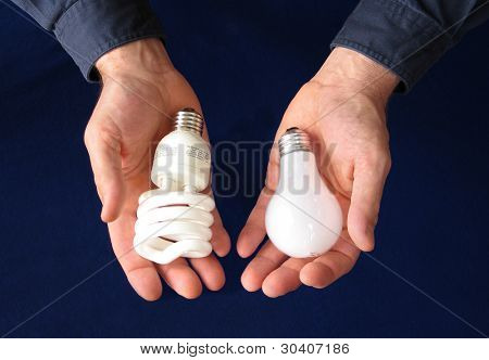 One hand holding a compact fluorescent bulb, the other an incandescent bulb, showing comparison