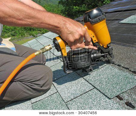 Tischler verwendet Bolzenschußgerät Asphalt Schindeln Dach an