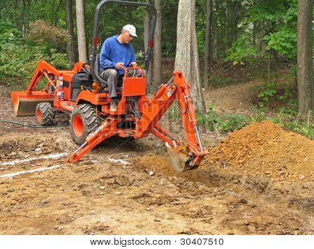 Man digging foundation trench with backhoe