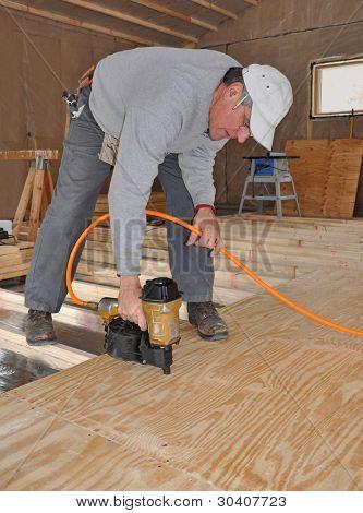 Mann Nageln Sperrholz Untergrund mit Bolzenschußgerät