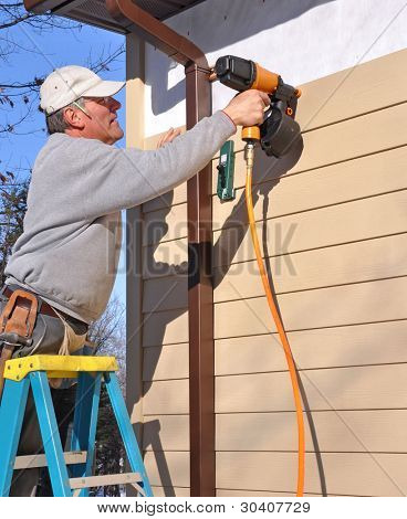 Man installing fibrous cement siding with nail gun poster