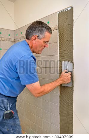 Man installing ceramic tiles in bathroom