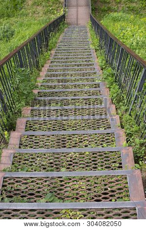 Metal Iron Staircase Leading Down. Metal Steps Iron Railings, Descending From A Green Grassy Hill. O