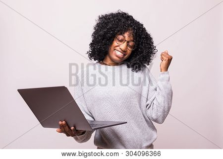 Portrait Of A Happy African Woman Using Laptop Computer Make Winner Gesture Posing Isolated Over Whi