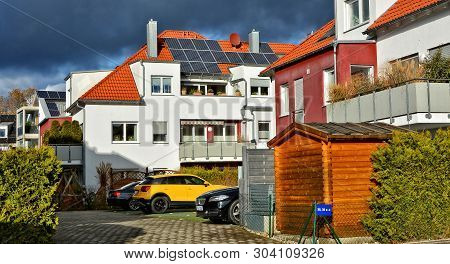 Modern Residential House With Solar Panels On A Red Tile Roof. Alternative Energy. Cars In A Yard. G