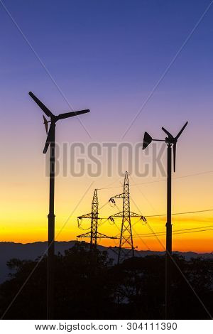 High Voltage Power Lines With Electricity Pylons At Twilight. At The Horizon Wind Turbines And A Nuc