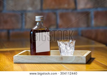 Ice In A Glass And Coffee In A Bottle Ready For Serve To Customer,brick Wall Background.