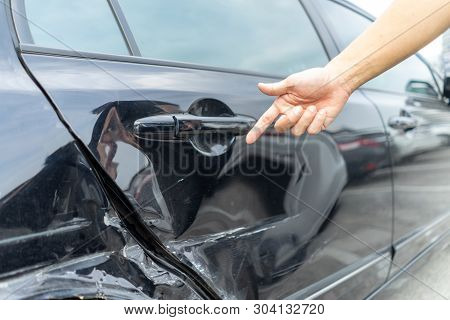 Man Hand Pointing On Car Bumper Dented Broken On Black Car Door. Vehicle Car Crash Damage Accident O