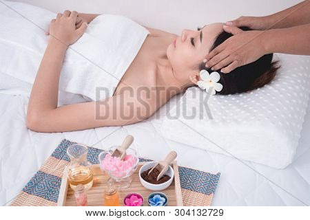 Female Relaxing Massage At Spa Wellness Center. Beautiful Woman Lying On Spa Bed. Young Asian Girl E