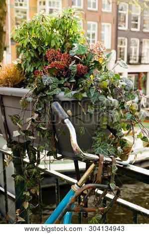 Old Bicycle Chained To A Amsterdam Cannal Bridge Decorated With Flowers.