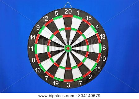 The Target For The Sport Of Darts, On A Blue Background. Darts Game In Which Players Rivals Throw Da