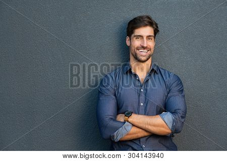 Young handsome man leaning against grey wall with arms crossed. Satisfied young businessman laughing and looking at camera. Portrait of happy stylish guy standing over grey background with copy space.