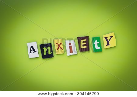 A Word Writing Text Anxiety From Cut Letters On A Green Background. Headline - Anxiety, Card Of Psyc