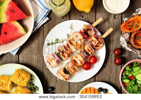Grilled Chicken And Vegetable Kabobs With A Frame Of Fruits, Salad And Potatoes. Top View Table Scen