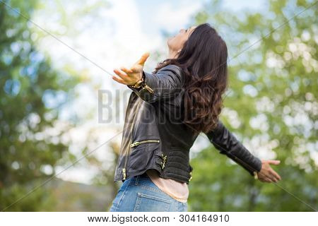 Beautiful Middle-age Woman In Black Leather Jacket Arms Wide Open. Springtime, Outdoors