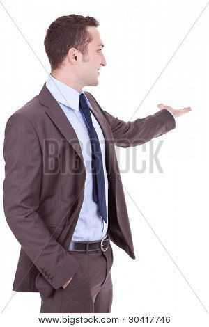 Happy business man giving presentation on white background . young businessman with his arm outstretched , showing you something at his back side