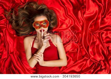 Woman In Venetian Mask Lying On Red Silk Fabric Background, Fashion Model Carnival Secret, Finger On