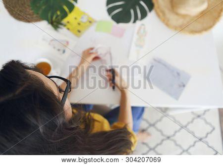 Young Brunette Woman Creating Her Feng Shui Wish Map Using Scissors