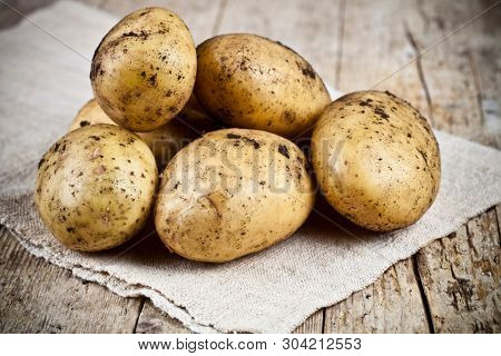 Fresh organic dirty potatoes heap closeup on linen tablecloth on rustic wooden background. Newly harvested potatoes.