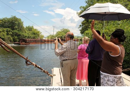 Main River Belize, Central America - Circa 2016 - Tourists Wave To Sugar Cane Barge As It Passes The